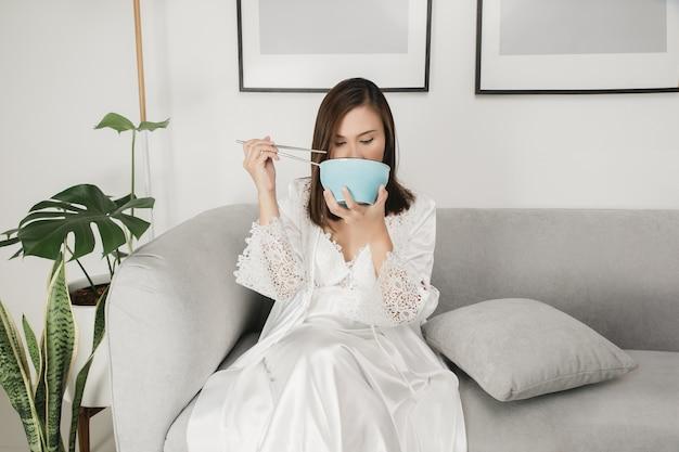 Mulher asiática em camisola de cetim branco sentada em um sofá cinza e comendo comida Foto Premium