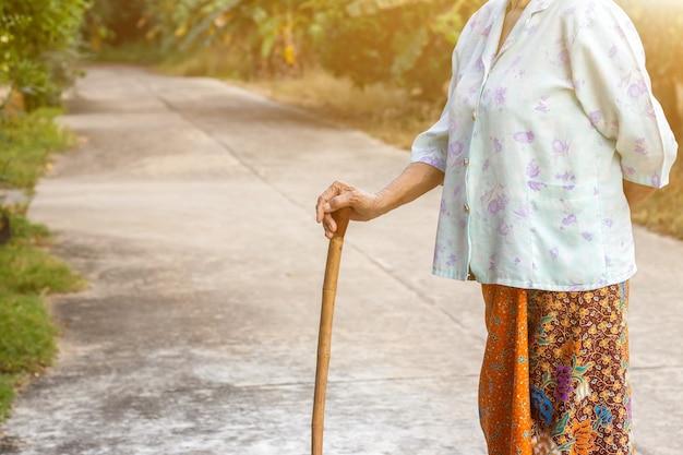 Mulher asiática em pé com as mãos em uma bengala Foto Premium