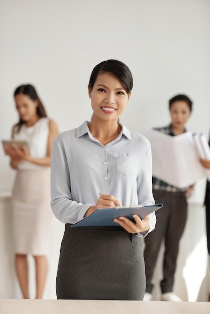 Mulher asiática em roupas inteligentes, posando no estúdio com a área de transferência e colegas no fundo Foto gratuita