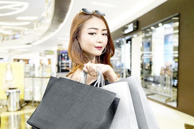 Mulher asiática em roupas pretas e óculos de sol carregando sacolas de compras no shopping Foto Premium