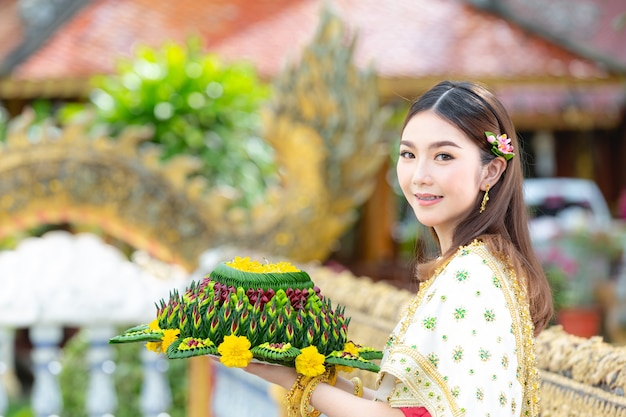 Mulher asiática em vestido tailandês tradicional realiza festival kratong loy krathong Foto gratuita