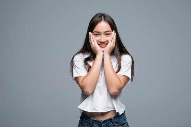 Mulher asiática encantador posando e olhando para longe sobre fundo cinza Foto gratuita