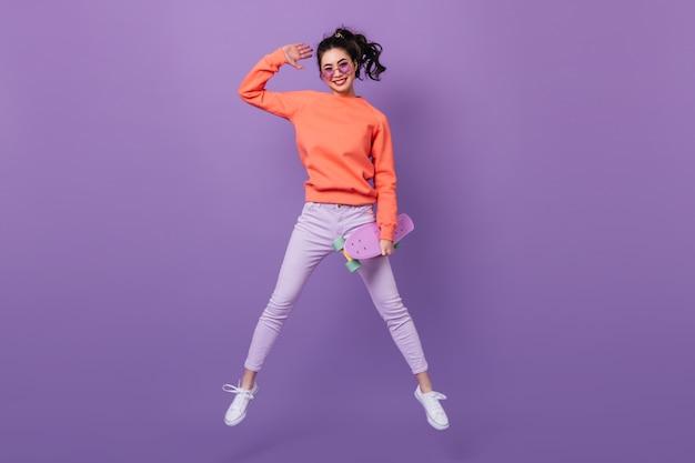 Mulher asiática engraçada em calças pulando sobre fundo roxo. visão de comprimento total de uma jovem coreana com longboard. Foto gratuita