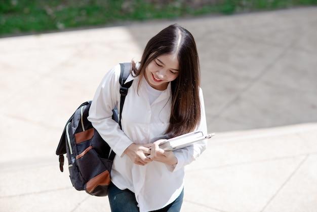 Mulher asiática estudante com laptop e bolsa, conceito de educação Foto gratuita