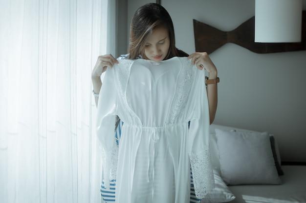Mulher asiática experimentando um novo robe de cetim branco em casa uma garota acaba de comprar uma nova roupa de dormir sexy de renda de seda Foto Premium