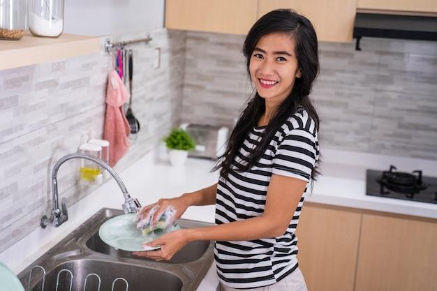 Mulher asiática fazendo uma limpeza de prato Foto Premium