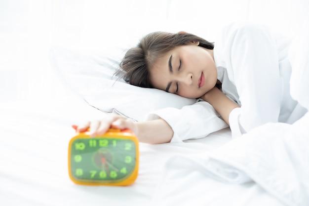 Mulher asiática feliz acordar e desligar o despertador tendo um bom dia Foto Premium