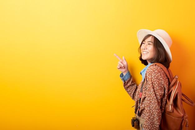 Mulher asiática feliz jovem turista na parede amarela Foto Premium