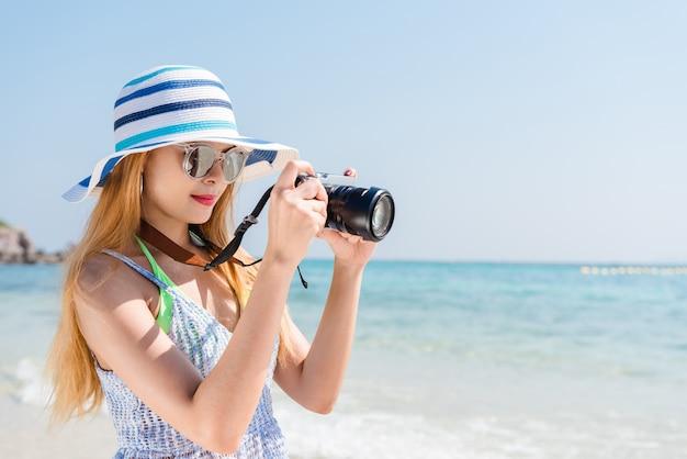 Mulher asiática feliz nas férias fotografando com uma câmera na praia com o horizonte no fundo. Foto gratuita