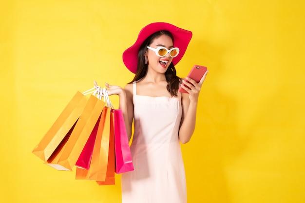Mulher asiática feliz que usa o telefone celular no fundo amarelo, conceito colorido da compra. Foto Premium