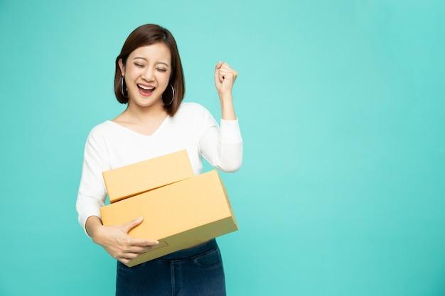 Mulher asiática feliz segurando uma caixa de pacote Foto Premium