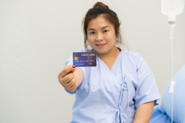Mulher asiática ficar no hospital e aparecer um cartão de crédito com o polegar para cima Foto Premium