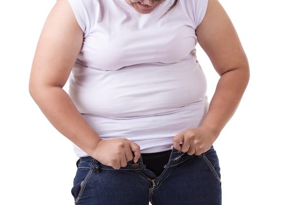Mulher asiática gorda tentando usar jeans tamanho pequeno Foto Premium