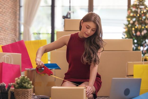 Mulher asiática gravando uma caixa de papelão Foto Premium