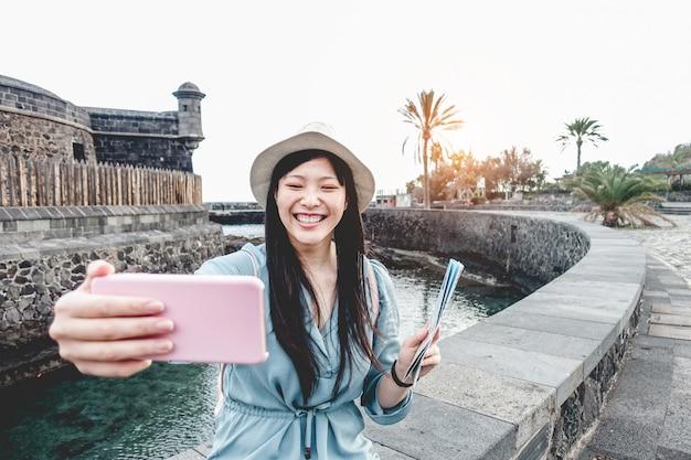 Mulher asiática influenciadora criando conteúdo com smartphone - menina chinesa se divertindo com a nova tecnologia de tendências - trabalho de atividade de geração milenar, conceito de juventude e tecnologia - foco no rosto Foto Premium