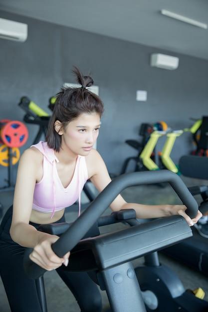 Mulher asiática jogar fitness no ginásio Foto gratuita