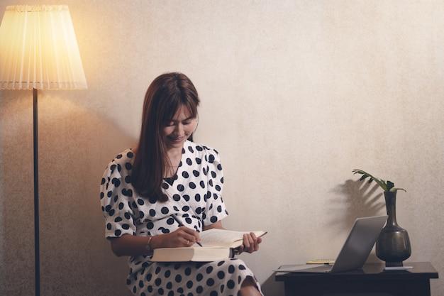 Mulher asiática lendo livro no tempo livre com feliz Foto Premium