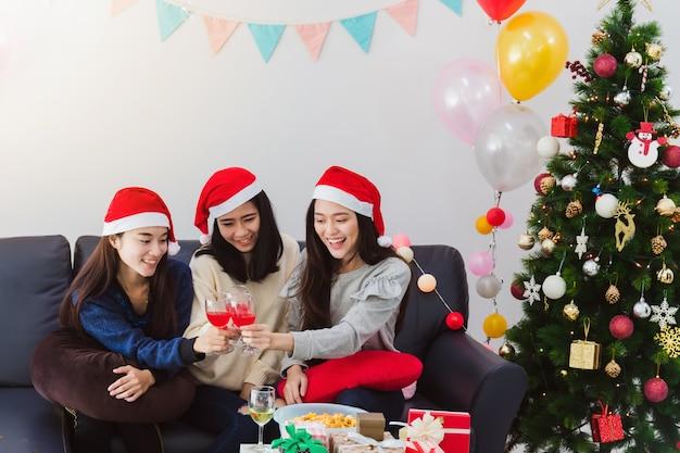 Mulher asiática linda jovem beber champanhe celebração com melhor amigo. cara sorridente no quarto com decoração de árvore de natal para o festival de férias. conceito de festa e celebração de natal. Foto Premium