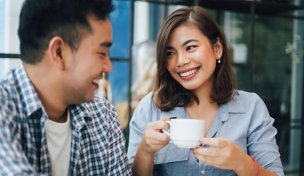 Mulher asiática na camisa azul no café, bebendo café e conversando com o namorado sorriso e cara feliz Foto Premium
