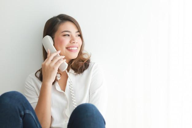 Mulher asiática na camisa branca usando telefone vintage falando, na sala de estar Foto Premium