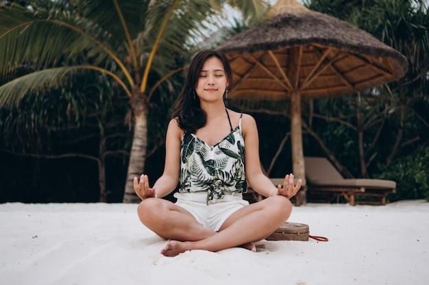 Mulher asiática na praia praticando ioga Foto gratuita