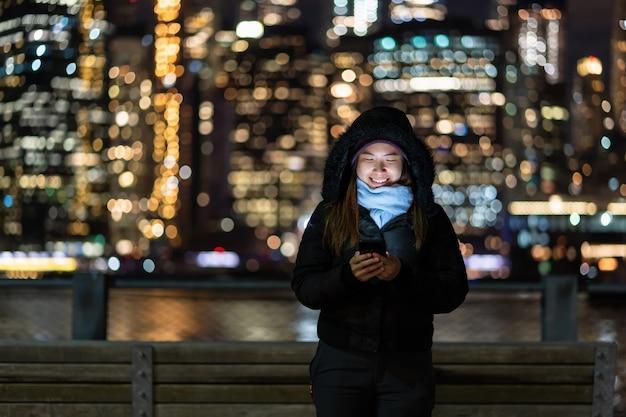 Mulher asiática no inverno terno usando telefone móvel esperto com sorriso ação sobre a foto turva bokeh Foto Premium