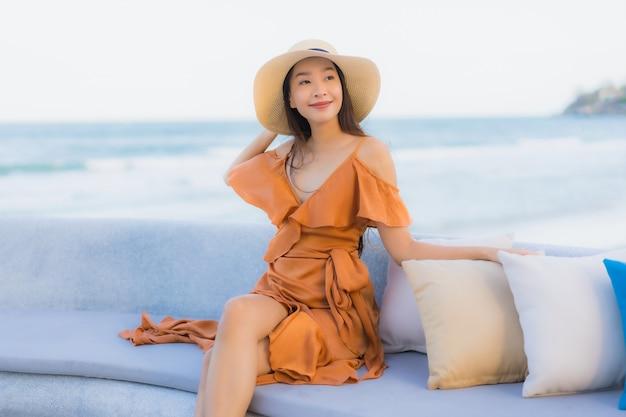 Mulher asiática no sofá perto da praia Foto gratuita