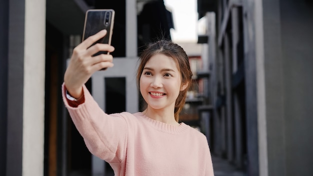 Mulher asiática nova bonita alegre do blogger do mochileiro que usa o smartphone que toma o selfie ao viajar no bairro chinês no pequim, china. Foto gratuita