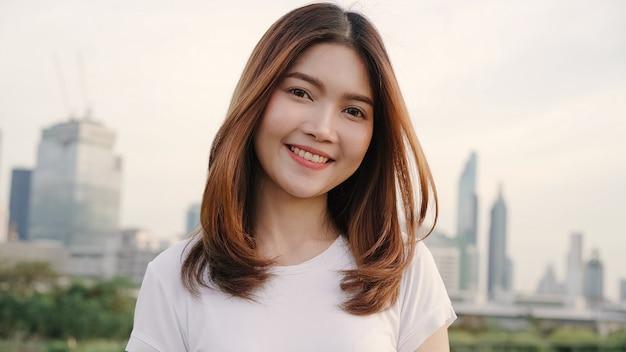 Mulher asiática nova bonita alegre que sente o sorriso feliz à câmera ao viajar na rua na cidade do centro. Foto gratuita