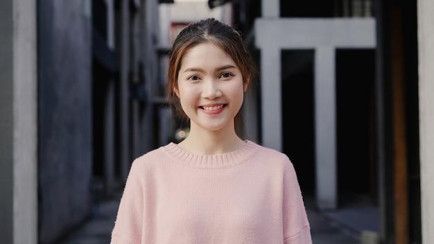 Mulher asiática nova bonita alegre que sente o sorriso feliz à câmera ao viajar no bairro chinês no pequim, china. Foto gratuita