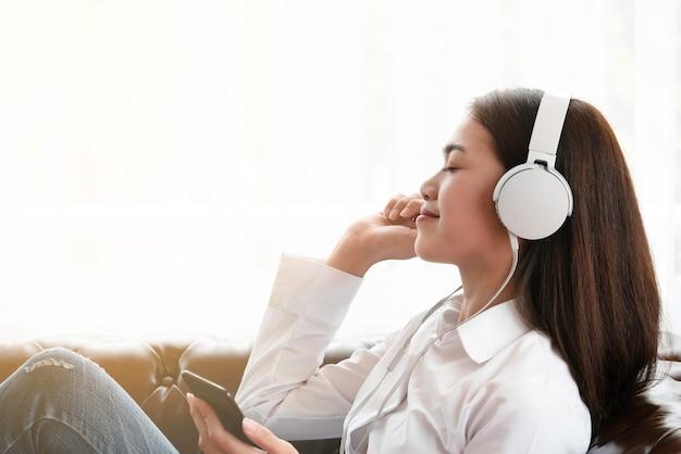 Mulher asiática nova bonita feliz usar o smartphone e a música de escuta no auscultadores. Foto Premium