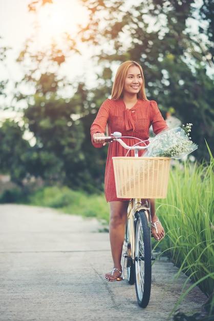 Mulher asiática nova bonita que monta uma bicicleta em um parque Foto gratuita