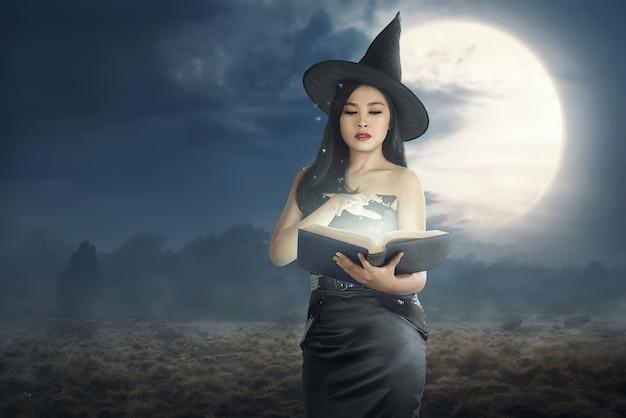 Mulher asiática nova da bruxa que lê os livros do período Foto Premium