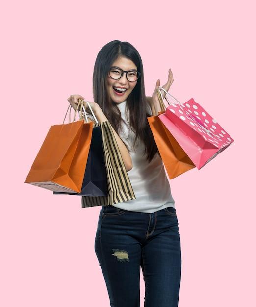 Mulher asiática nova feliz que compra no sentimento feliz e que guarda o saco de papel do produto Foto Premium