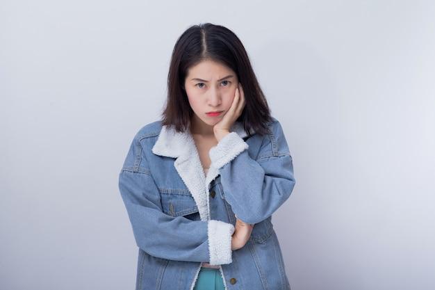 Mulher asiática nova irritada que sente a emoção negativa e má Foto Premium
