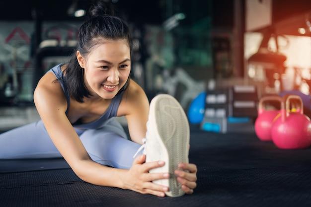 Mulher asiática nova no estilo de vida saudável do gym que senta-se na esteira da ioga que guarda o pé que estica o pé. Foto Premium