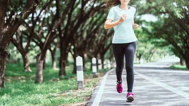 Mulher asiática nova que corre na estrada na natureza. Foto Premium