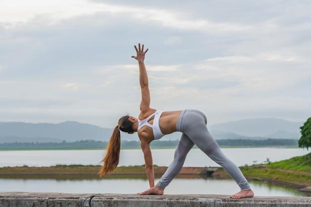 Mulher asiática nova que faz a ioga no banco de rio. Foto Premium
