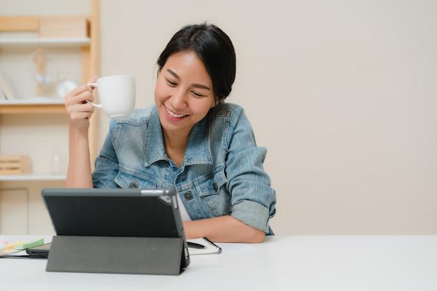 Mulher asiática nova que trabalha usando a tabuleta que verifica meios sociais e que bebe o café quando relaxe na mesa na sala de visitas em casa. Foto gratuita