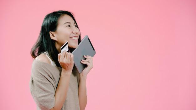 Mulher asiática nova que usa a tabuleta que compra a compra em linha pelo cartão de crédito que sente o sorriso feliz na roupa ocasional sobre o tiro cor-de-rosa do estúdio do fundo. Foto gratuita