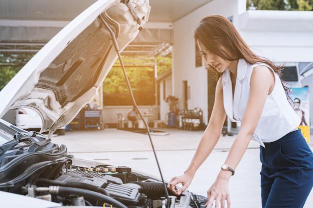 Mulher asiática, o carro está quebrado. abra o capô, verifique o motor. Foto Premium