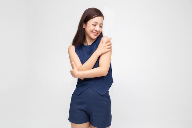 Mulher asiática ocasional nova feliz que abraça-se isolada no branco. ame a si mesmo Foto Premium