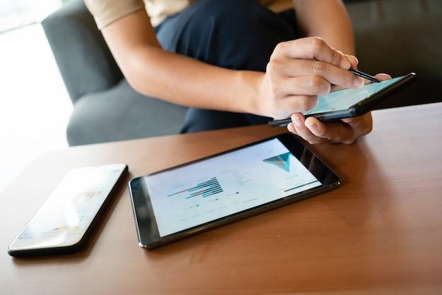 Mulher asiática olhando alguns gráficos em seu telefone celular enquanto está sentado na cafeteria Foto Premium