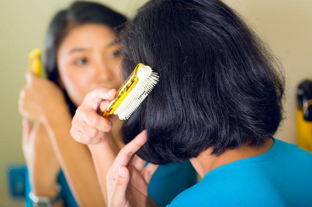 Mulher asiática, pentear o cabelo no espelho do banheiro Foto Premium