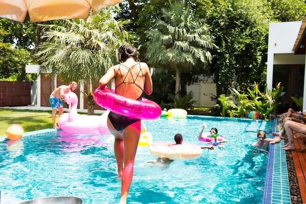 Mulher asiática pulando para a piscina com tubo inflável Foto Premium
