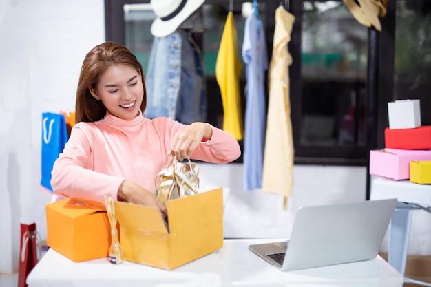 Mulher asiática que embala seu produto ao sentar-se no conceito do negócio do comércio eletrônico da oficina. Foto Premium
