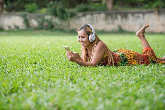 Mulher asiática que escuta música favorita em fones de ouvido. feliz tempo e relaxe. Foto gratuita