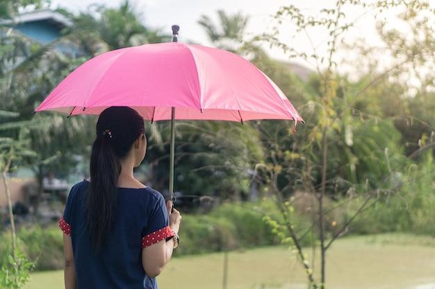 Mulher asiática que está com o guarda-chuva cor-de-rosa no parque. Foto Premium