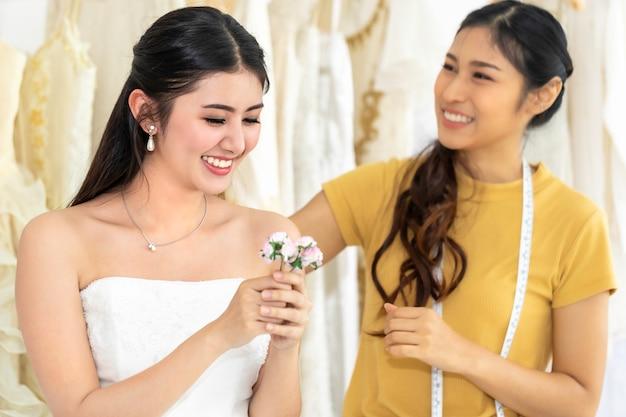 Mulher asiática que guarda a flor que mede no vestido de casamento em uma loja pelo alfaiate. Foto Premium