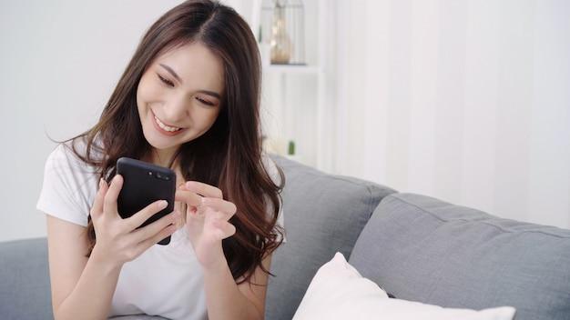 Mulher asiática que joga o smartphone ao encontrar-se no sofá home em sua sala de visitas. Foto gratuita